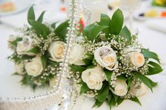 在篮子backgraound花束花上升了/婚戒的美丽的白色婚礼花束 免版税库存图片