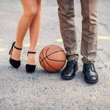 在篮球场的男性和女性腿 免版税库存图片