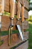 在篱芭上的园艺工具 免版税库存照片