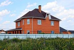 在篱芭之外的现代棕色砖房子在草 免版税库存图片