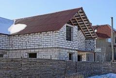 在篱芭后的大未完成的白色砖房子在雪 库存图片