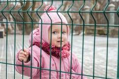在篱芭后的小美丽的女孩婴孩,栅格在一个盖帽和一件夹克锁了激动哀伤的在他的面孔 免版税库存照片