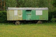 在篱芭后的庭院里电烙有被锤击的窗口的容器在轮子 库存图片
