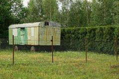 在篱芭后的庭院里电烙有被锤击的窗口的容器在轮子 免版税库存照片