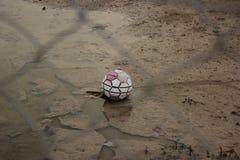 在篱芭后的老足球 图库摄影
