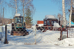 在篱芭后的被放弃的老拖拉机 库存照片