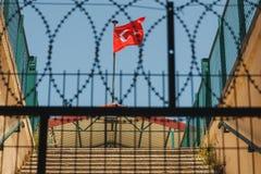 在篱芭和铁丝网后的土耳其旗子 免版税库存照片