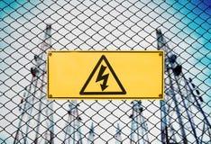在篱芭导线的高压标志和标志小心牌在电能厂驻地 免版税库存图片