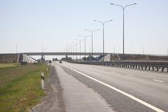 在篱芭左边的高速公路在被弄脏的背景中,汽车来临 免版税库存图片