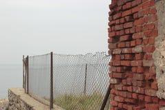 在篱芭旁边的红砖墙壁 免版税库存照片