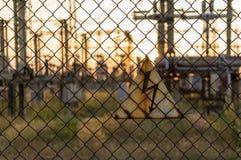 在篱芭的危险标志在背景电子分站 免版税库存照片
