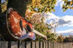 在篱芭的吉他 库存图片