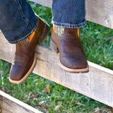在篱芭的牛仔靴 库存图片