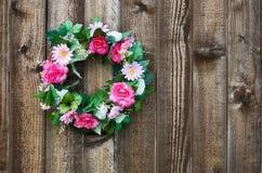 在篱芭的花卉花圈 免版税库存图片