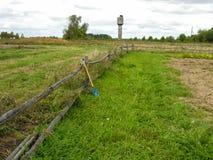 在篱芭的蓝色铁锹在土豆领域的边缘 库存照片