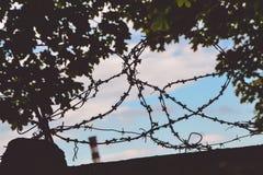 在篱芭的铁丝网以工厂管子、树叶子和多云天空为背景 库存照片