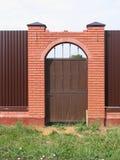 在篱芭的门有砖柱子的 免版税库存图片