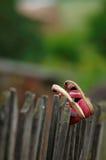 在篱芭的破旧的孩子鞋子 免版税库存照片