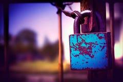 在篱芭铁的蓝色破旧的锁在蓝色和紫罗兰色葡萄酒颜色 库存照片