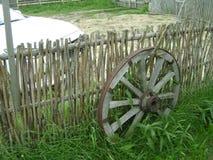 在篱芭附近的马车车轮 库存图片