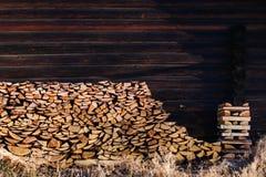 在篱芭附近被堆积的木柴 免版税库存图片
