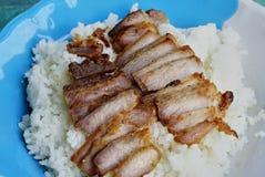 在米上把放的油煎的切的猪肉 库存照片