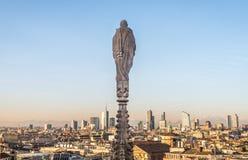 在米兰圆顶屋顶的哥特式尖顶与城市风景的作为背景 米兰,意大利 库存图片