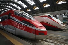 在米兰的中央火车站的两现代高速火车 免版税库存图片
