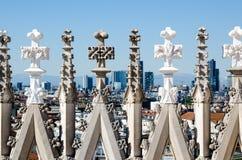在米兰的圆顶屋顶的雕塑与米兰风景的在背景中 免版税库存照片