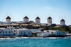 在米科诺斯岛的五台风车有前景的海的 图库摄影