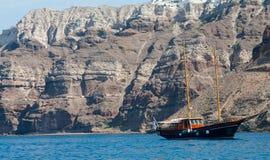 在米科诺斯岛的峭壁下被停泊的游艇 图库摄影