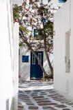在米科诺斯岛的胡同有蓝色门的在背景中 免版税图库摄影