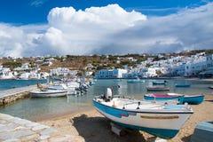 在米科诺斯岛,希腊加速在海海滩的小船 有白色房子的海村庄山风景的 暑假 库存图片