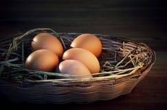 在米秸杆的新鲜的鸡蛋有棕色木背景 免版税库存照片