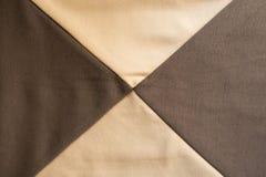 在米黄和棕色织品之间的X型缝 图库摄影
