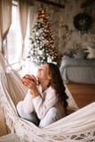 在米黄毛线衣和裤子打扮的微笑的深色头发的女孩拿着坐在舒适的一个吊床的一个红色杯子装饰 库存图片