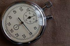 在米黄牛仔裤背景,价值措施时间、老时钟箭头分钟和第二个准确性定时器纪录的秒表 免版税图库摄影