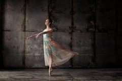 在米黄礼服的年轻美丽的跳芭蕾舞者 免版税库存照片