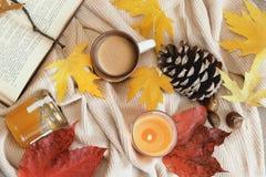 在米黄羊毛背景的秋天框架平的被放置的构成 枫叶,季节coffe,开放书,橙色芳香蜡烛,pinec 免版税图库摄影