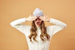 在米黄背景的白色被编织的毛线衣和帽子和太阳镜富人乐趣打扮的滑稽的女孩在演播室 库存照片