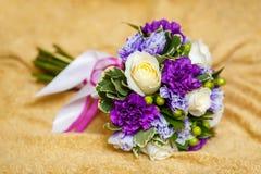 在米黄背景,婚姻概念的紫色婚礼花束 库存图片