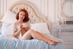 在米黄葡萄酒女用贴身内衣裤打扮的夫人的一个豪华别针摆在她的卧室和食用一个杯子早餐茶 免版税库存图片