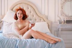 在米黄葡萄酒女用贴身内衣裤打扮的夫人的一个豪华别针摆在她的卧室和食用一个杯子早餐茶 库存图片