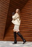 在米黄被编织的礼服、短的紧身连衫外套、手套和起动步行打扮的时髦的女孩在公园在好日子 库存图片
