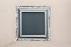 在米黄墙壁上的方形的窗口 库存照片