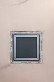 在米黄墙壁上的方形的窗口 图库摄影
