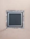 在米黄墙壁上的方形的窗口 免版税库存图片