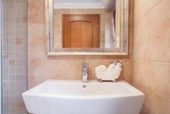 在米黄洗手间的陶瓷水盆 免版税库存图片
