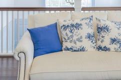 在米黄沙发的蓝色枕头在豪华客厅 库存照片