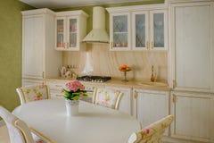 在米黄牧人颜色的经典样式厨房和餐厅内部 库存图片